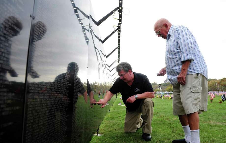 Vietnam Veterans Memorial Fund's Bill Kearsing helps Ken Micklus, of West Haven, find a name on The Wall That Heals, which is a half-scale replica of The Vietnam Veterans Memorial Wall in Washington D.C., set up at Savin Rock Park in West Haven, Conn. on Thursday October 20, 2016. The wall holds the names of 58,307 members of the military, which includes both killed and missing in action. It will be on display until Sunday Oct. 23 with a ceremony at noon. Photo: Christian Abraham / Hearst Connecticut Media / Connecticut Post