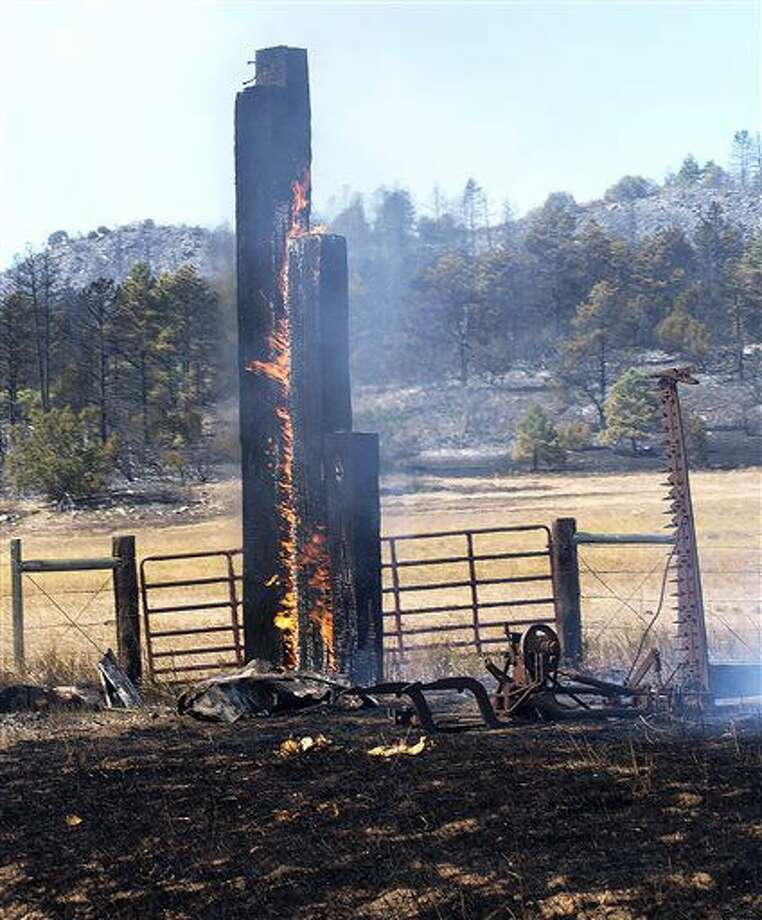 A gate post burns, Tuesday, Oct. 4, 2016 in Beulah, Colo. on Oct. 4, 2016. A wildfire that has forced hundreds from their homes in southern Colorado destroyed seven homes, but authorities were hopeful Tuesday that they can get a handle on the blaze. (John Jaques/The Pueblo Chieftain via AP)