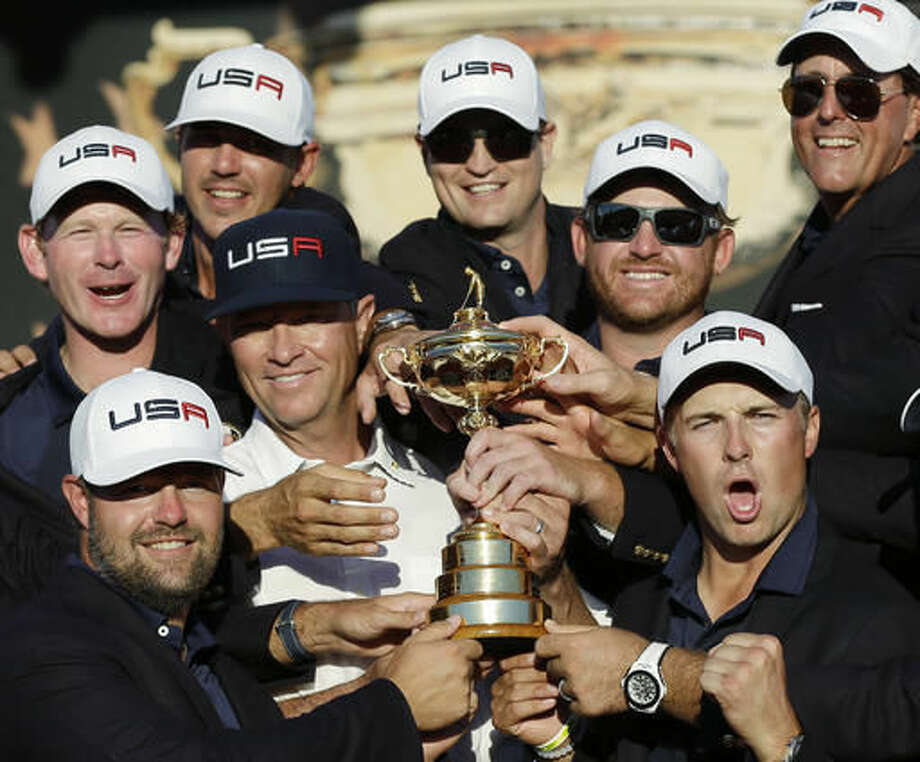 United States captain Davis Love III is surrounded by his players as they pose for a picture during the closing ceremony of the Ryder Cup golf tournament Sunday, Oct. 2, 2016, at Hazeltine National Golf Club in Chaska, Minn. (AP Photo/David J. Phillip)