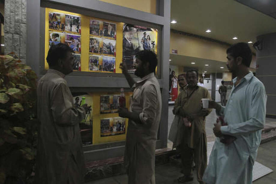 Pakistani cinema-goers look at photos displayed at a local cinema in Karachi, Pakistan, Saturday, Oct. 1, 2016. Pakistani cinemas have stopped showing Indian films after India banned Pakistani actors from its movie industry amid soaring tensions between the two nuclear-armed rivals over Kashmir, cinema owners said Saturday. (AP Photo/Fareed Khan)