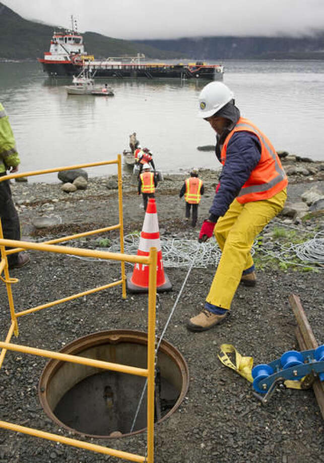 In this Sept. 23, 2016 photo Davy Chan, of International Telecom, pulls a guide line where a fiber optic cable is being brought to shore in Haines, Alaska, for the Alaska Power and Telephone Company. The cable is the first fiber-optic link between Juneau and the northern end of Lynn Canal and the first significant undersea fiber link constructed by AP&T. When it begins operating in mid-October, it will bring faster, more reliable internet service to Haines and Skagway, and possibly to Juneau and the Yukon.(Michael Penn /The Juneau Empire via AP)