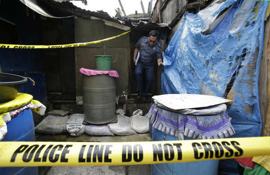 """A policeman comes out of the shanty home of two brothers and an unidentified man who were killed during an operation as part of the continuing """"War on Drugs"""" campaign of Philippine President Rodrigo Duterte in Manila, Philippines on Thursday, Oct. 6, 2016. An independent poll released Thursday showed that more than three-quarters of Filipinos are satisfied with President Duterte, even though he is under fire internationally for his deadly crackdown on suspected drug dealers and users. (AP Photo/Aaron Favila)"""