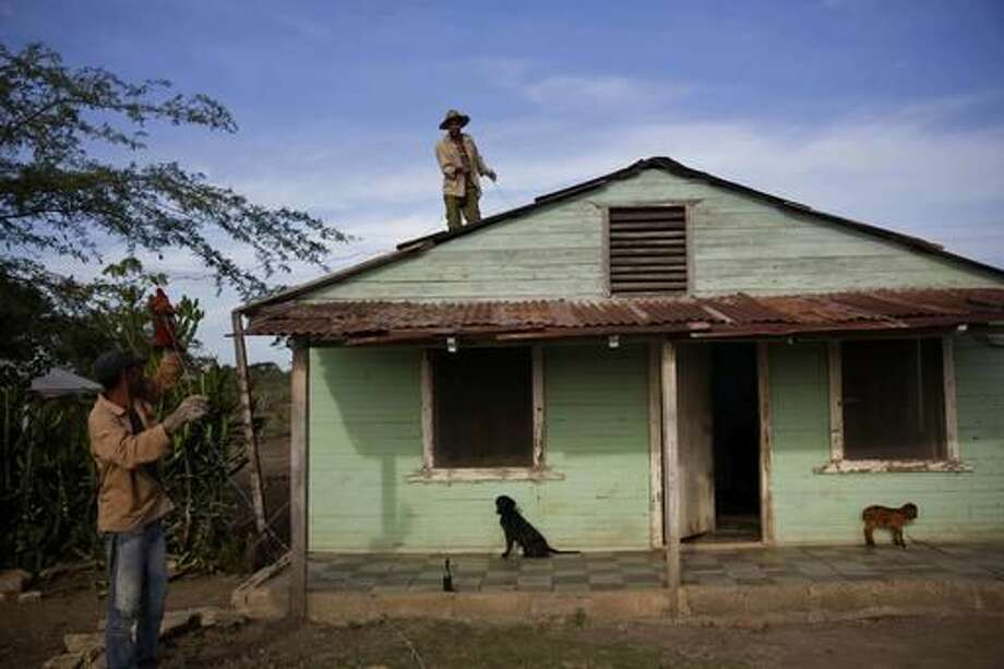 Residents secure the roof of their wooden house prior the arrival of Hurricane Matthew, in the village Paraguay, Guantanamo, Cuba, Monday, Oct. 3, 2016, A hurricane warning is in effect for Jamaica, Haiti, and the Cuban provinces of Guantanamo, Santiago de Cuba, Holguin, Granma and Las Tunas - as well as the southeastern Bahamas. (AP Photo/Ramon Espinosa)