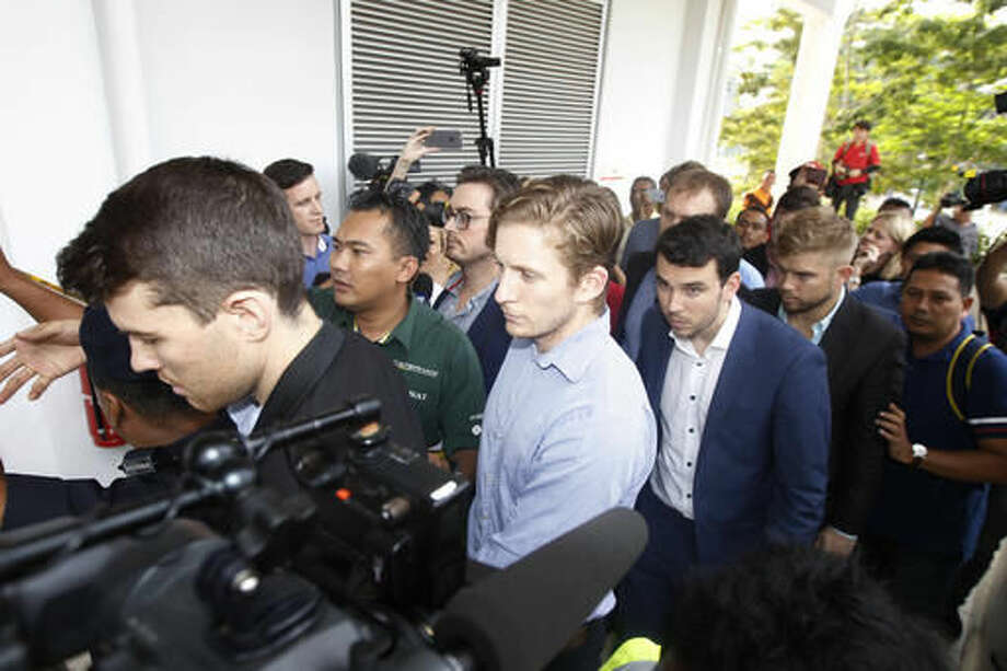 James Paver, left, Nick Kelly, third left with glasses, Thomas Whitworth, fourth left, Branden Stobbs, third right, of the nine Australian men arrested arrive at the Sepang Magistrate in Sepang, Malaysia, Thursday, Oct. 6, 2016. Nine Australian friends who have spent four nights in Malaysian police detention will appear in a court for the first time on Thursday after stripping down to their briefs and drinking beer from shoes at the Malaysian Formula One Grand Prix, an official said. (AP Photo/Joshua Paul)