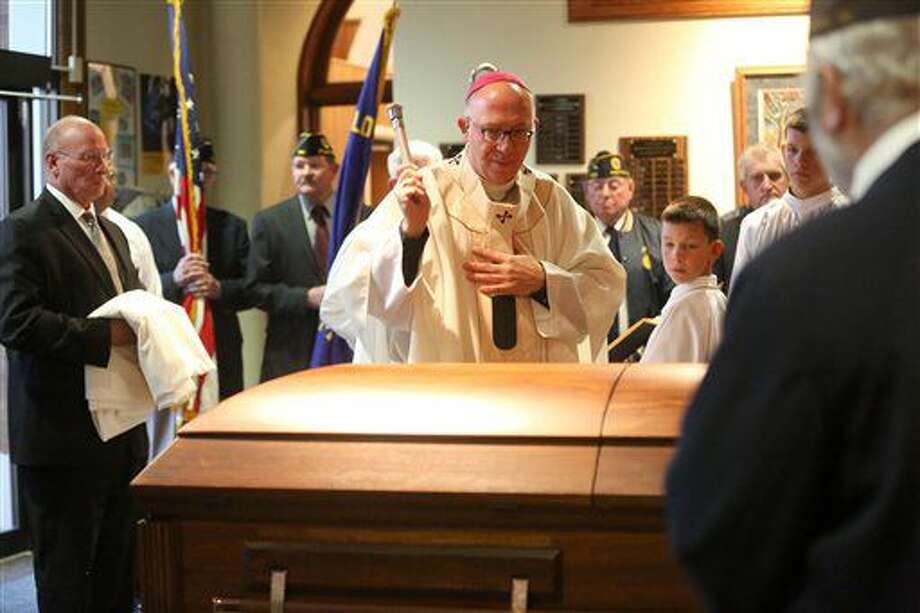 Dubuque Archbishop Michael Jackels leads a Mass of remembrance for Chaplain Aloysius Schmitt on Wednesday, Oct. 5, 2016, at St. Luke's Church in St. Lucas, Iowa. Schmitt, a St. Lucas, native, died on Dec. 7, 1941, when the Japanese attacked Pearl Harbor. After nearly 75 years, his remains have been identified. (V/Telegraph Herald via AP)