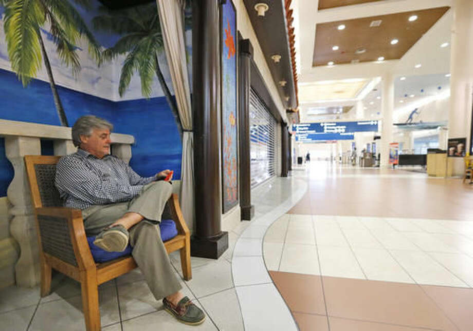 Steff Chalk checks his phone as he waits at the Palm Beach International airport after the hotel he was going to stay in was evacuated as Hurricane Matthew advances, Thursday, Oct. 6, 2016, in West Palm Beach, Fla. The National Hurricane Center in Miami said the storm's maximum sustained winds had strengthened to 140 mph as of late Thursday morning and were expected to maintain their strength as the storm approaches the Florida coast. (AP Photo/Wilfredo Lee)