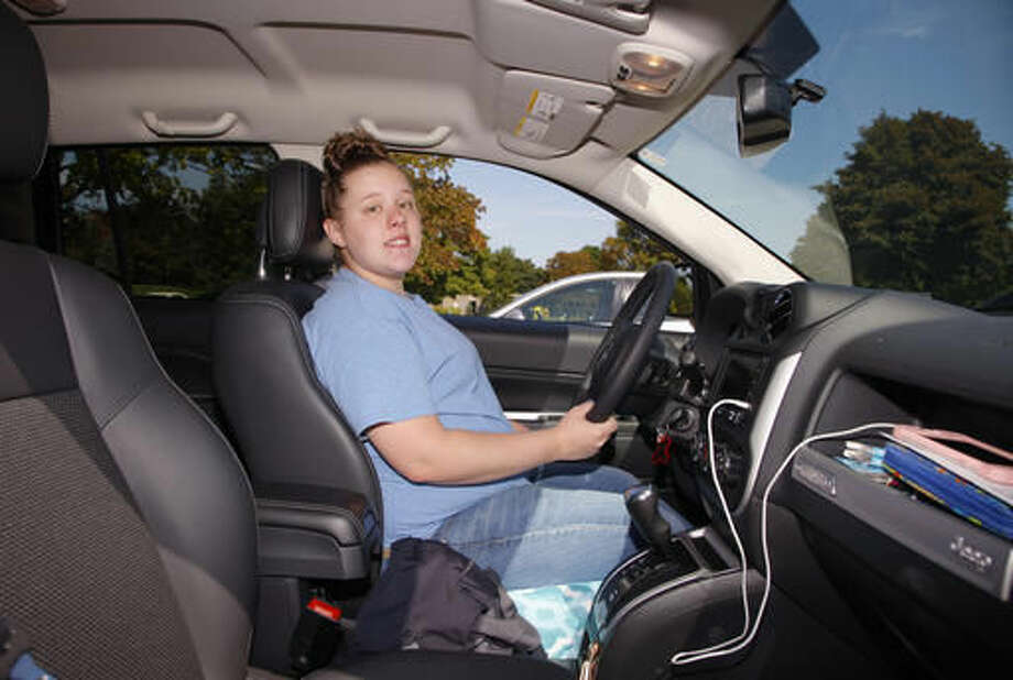 In this Friday, Aug. 26, 2016, photo, Alaina Dishman poses with her new Jeep Compass, in Delta Township, Mich., near Lansing. Dishman was among those who didn't have enough credit to buy a new car when she went to a showroom last summer. But a salesman got her into a program that helps young people build credit. (AP Photo/Al Goldis)