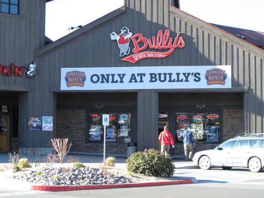 FILE - In this Feb. 24, 2015, file photo, visitors to a shopping strip mall in north Sparks walk in front of a Bully's Sports Bar & Grill in Sparks, Nev. Bully's Sports Bar & Grill has agreed to pay $375,000 in back wages to settle part of a class-action lawsuit with 15 cooks who accused the oldest sports bar chain in northern Nevada of denying them overtime pay in violation of federal labor laws. (AP Photo/Scott Sonner, file)