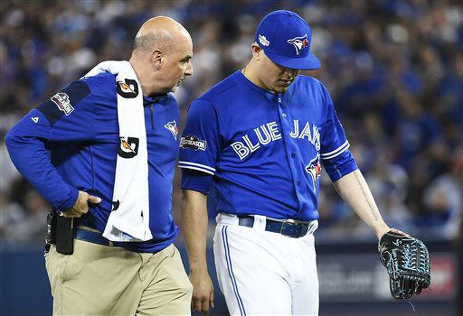 Toronto Blue Jays' Roberto Osuna, right, leaves the game with trainer George Poulis during the tenth inning of an American League wild-card baseball game against the Baltimore Orioles in Toronto, Tuesday, Oct. 4, 2016. (Nathan Denette/The Canadian Press via AP)