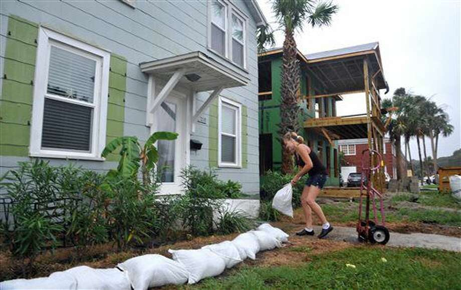 Rene Anger fills and stacks sandbags in front of her Cherry Street home in Neptune Beach, Fla., Wednesday, Oct. 05, 2016 as Hurricane Matthew approaches. (Bruce Lipsky/The Florida Times-Union via AP)