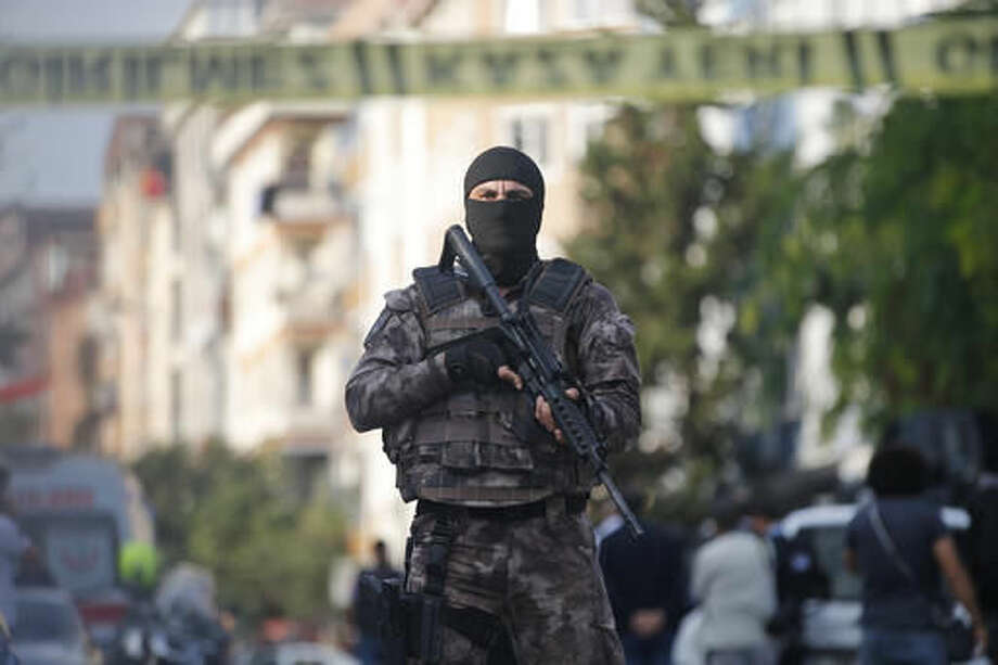 A masked Turkish police officer cordons off the area of a blast in Istanbul, Thursday, Oct. 6, 2016. A bomb placed on a motorcycle has exploded near a police station Thursday, wounding several people, Vasip Sahin, the governor for Istanbul, said. (AP Photo/Emrah Gurel)