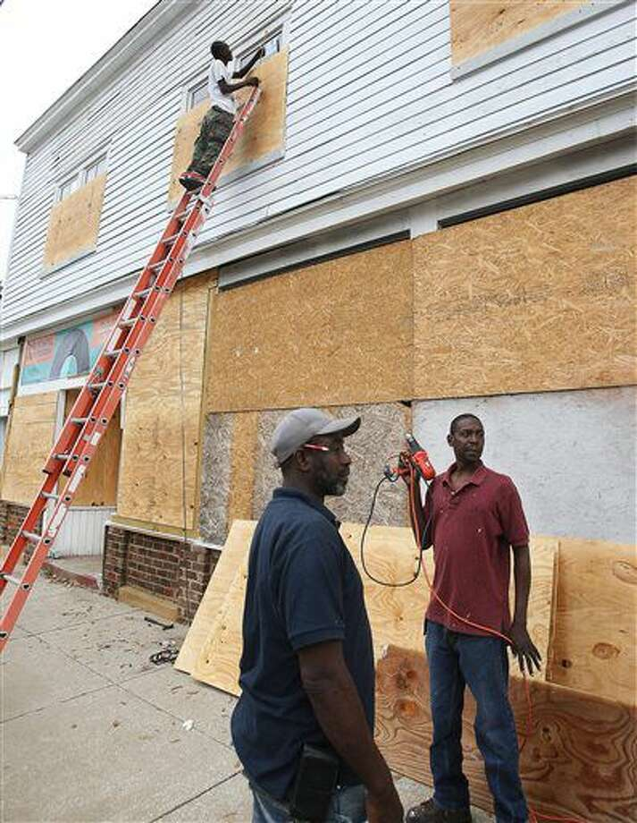 Henry Mack on the ladder Darrin Green and Ronald Brown are in the process of installing boards on the windows and doors of a property in Charleston, S.C., Wednesday, Oct. 5, 2016, to protect it from storm damage. Leroy Burnell/The Post and Courier via AP)