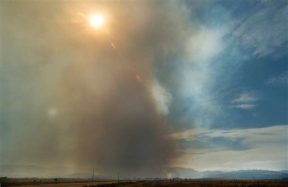 Smoke billows into the sky near Beulah, Colo., during a wildfire that began in the early afternoon on Monday, Oct, 3, 2016 near the small mountain town west of Pueblo, Colo. Students were evacuated from the local school and many residents were unable to get to their homes and livestock after the main road into town was closed. (Chris McLean/The Pueblo Chieftain via AP)