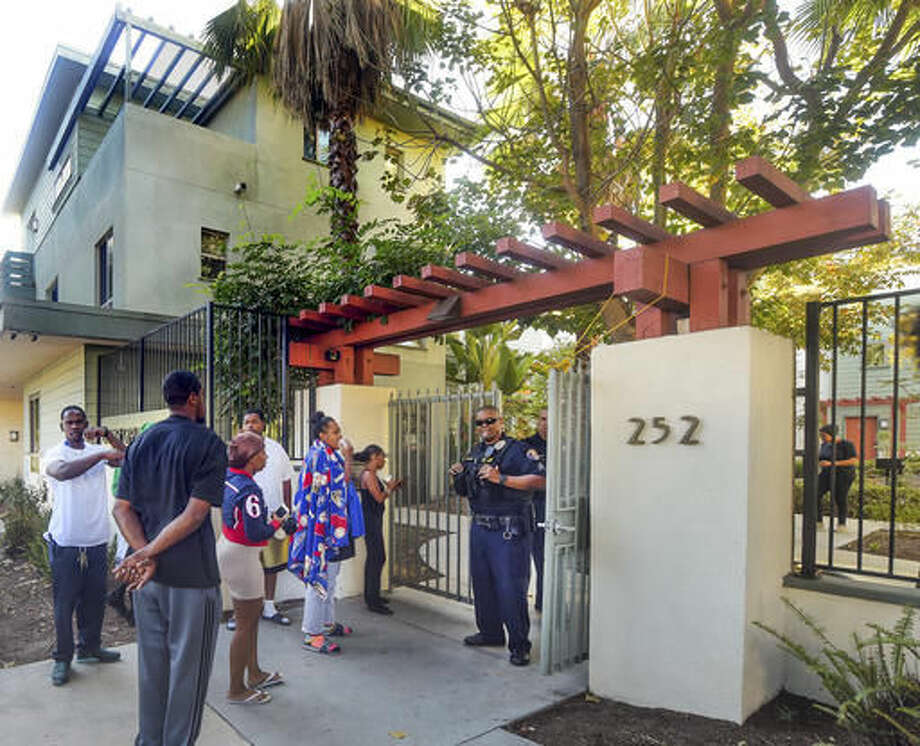 Shaney Lindsey, middle, covered with a sporting towel, as she waits outside the entrance of Orange Grove Gardens where her husband died in Pasadena, Calif., early Friday morning, Sept. 30, 2016. A man armed with a knife and reported to be bipolar died after a struggle with Pasadena police officers who were called to an apartment early Friday following reports of a disturbance. Pasadena police Chief Phillip Sanchez said a fight ensued after the officers used a Taser on the man when he ignored their orders to drop the knife. (Walt Mancini/The Pasadena Star-News via AP)