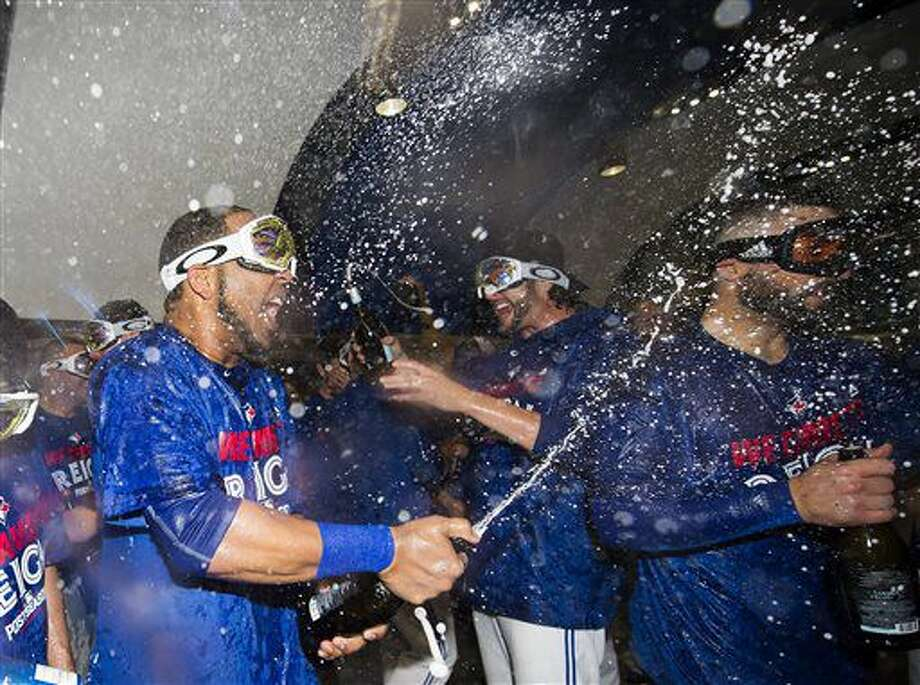 Toronto Blue Jays designated hitter Edwin Encarnacion, left, who hit the game winning three-run home run, celebrates with teammates after an American League wild-card baseball game against the Baltimore Orioles in Toronto, Tuesday, Oct. 4, 2016. (Nathan Denette/The Canadian Press via AP)