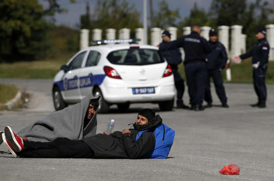 Migrants rest at a local gas station near the town of Indjija, about 40 kilometers (24 miles) north of the Belgrade, Serbia, Wednesday, Oct. 5, 2016. More than one hundred migrants who set off on foot toward the Hungarian border have agreed to end their protest march, demanding the border to be opened for people fleeing war and poverty, and return to the Serbian capital of Belgrade after spending the night out in the open. (AP Photo/Darko Vojinovic)