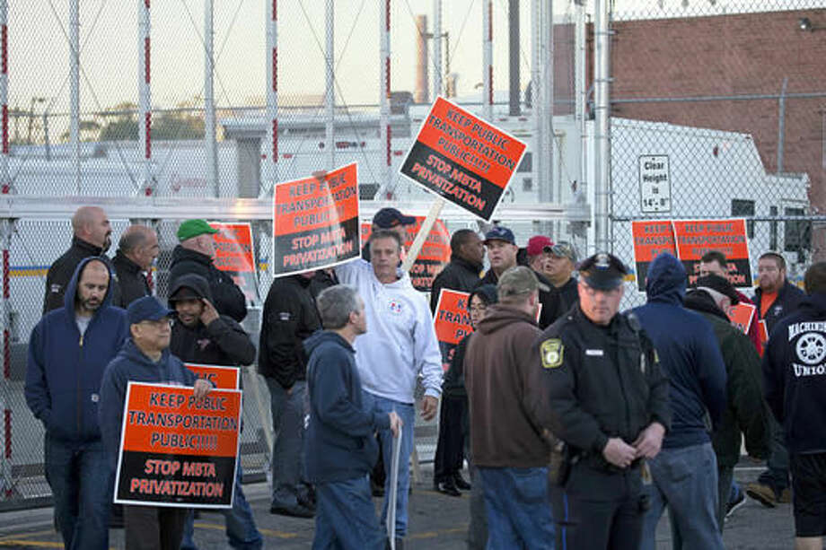 "Members of the MBTA's Carmen's Union protest outside the Massachusetts Bay Transportation Authority's so-called ""money room "" Thursday, Oct. 6, 2016 in the Charlestown facility in Boston. The MBTA plans to recommend to its fiscal control board on Thursday that Virginia-based Brink's be awarded a five-year, $18.7 million contract to oversee the Charlestown facility. (Mark Garfinkel/The Boston Herald via AP)"
