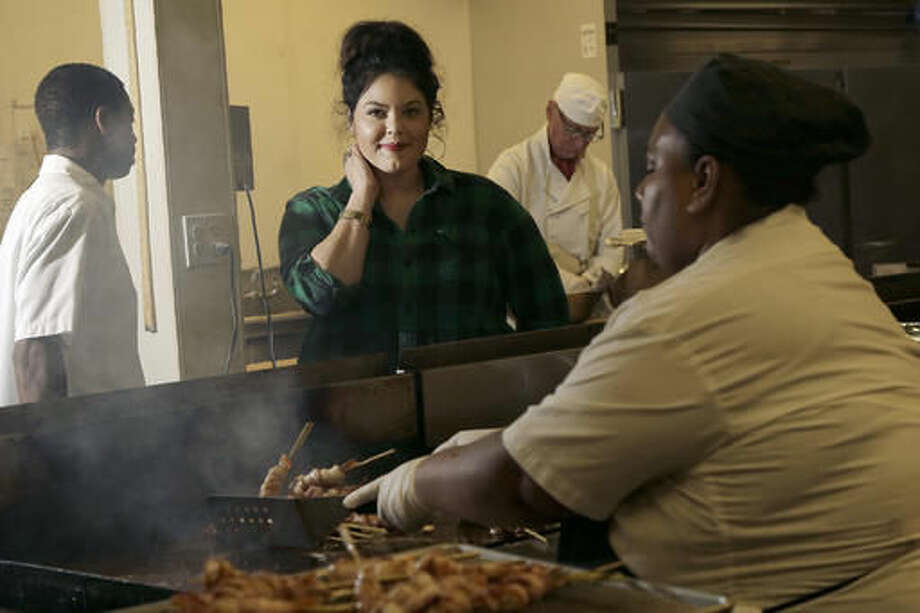 In this Wednesday, Sept. 28, 2016, photo, Olivia Colt, owner of catering company Salt & Honey, center, poses for photos as members of her cooking staff work in the kitchen in Berkeley, Calif. The campaign to give workers time off when they're sick is picking up momentum. Before California enacted its law, Colt had given paid leave to her salaried managers as a way to retain employees in an industry with high turnover. Now, hourly employees get sick leave as well, accruing one hour for each 30 hours they work. Colt sees several benefits: She has less staff turnover, and her 20 workers take better care of their health. (AP Photo/Jeff Chiu)