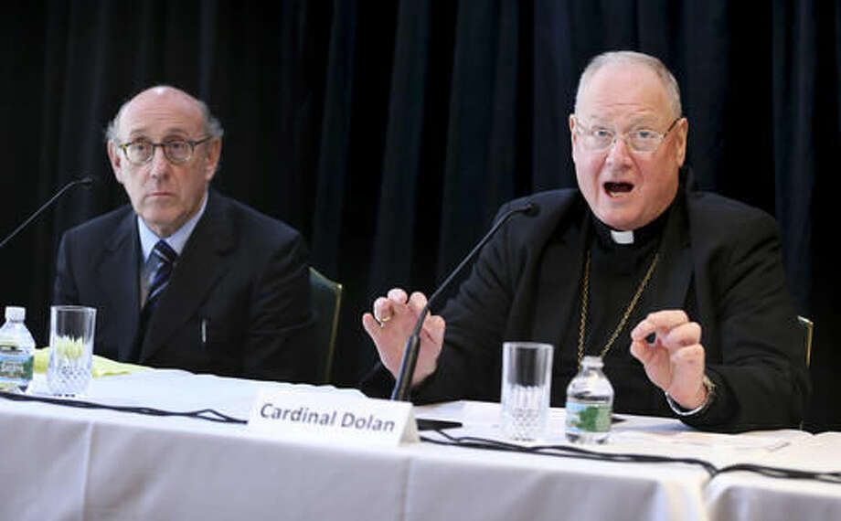 Cardinal Timothy Dolan, Archbishop of New York, speaks to reporters during a news conference in New York, Thursday, Oct. 6, 2016 as Kenneth Feinberg, left, listens. Dolan helped to announce a new program intended to provide reconciliation and compensation for victims of sexual abuse by clergy; Feinberg will administer the independent program. (AP Photo/Seth Wenig)