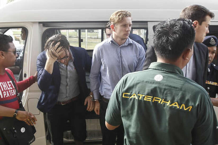Nick Kelly, second left, and Thomas Whitworth, center, two of the nine Australian men arrested arrives at the Sepang Magistrate in Sepang, Malaysia, Thursday, Oct. 6, 2016. Nine Australian friends who have spent four nights in Malaysian police detention will appear in a court for the first time on Thursday after stripping down to their briefs and drinking beer from shoes at the Malaysian Formula One Grand Prix, an official said. (AP Photo/Joshua Paul)