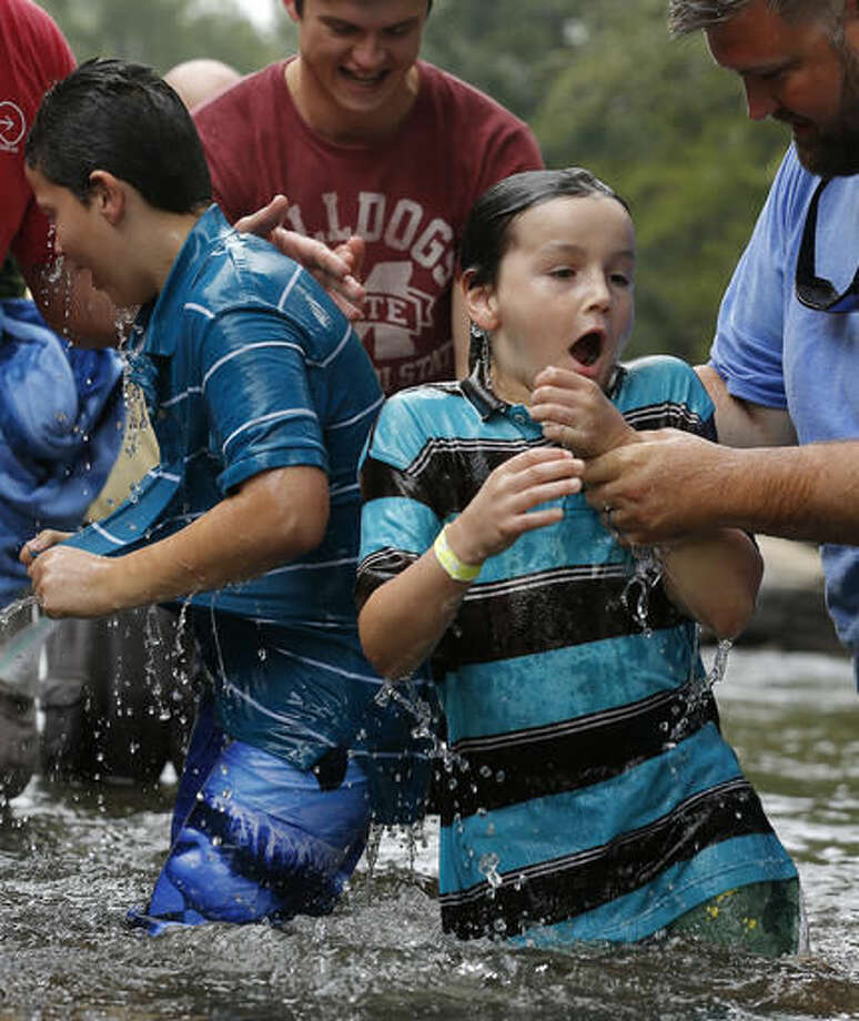 Brothers Will, 10, left, and Bowe Roberts, 9, react after being baptized in the Chattahoochee River, Sunday, Sept. 18, 2016, near Demorest, Ga. The ancient sacrament is memorialized in the Gospel account of John baptizing Jesus in the Jordan River. (AP Photo/Mike Stewart)