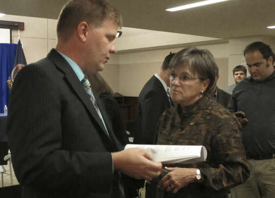 Kansas Budget Director Shawn Sullivan, left, confers with state Sen. Laura Kelly, D-Topeka, following a news conference about proposed changes in how the state forecasts how much money it expects to collect in taxes, Tuesday, Oct. 4, 2016, at the Statehouse in Topeka, Kan. The changes were proposed by a task force and include a recommendation that the state end monthly reports on how well tax collections stack up against projections (AP Photo/John Hanna)