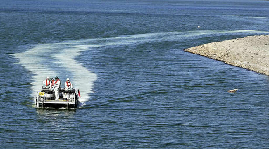 FILE - In this Sept. 14, 2006 file photo, a mixture of solvent and rotenone trails a pontoon boat as Oregon Department of Fish and Wildlife crews release the liquid into Diamond Lake to kill tui chub that had invaded the lake. Oregon Department of Fish and Wildlife officials purposely poisoned Diamond Lake. They weren't acting out of pure evil, however, but as a way to eradicate the invasive species that had been destroying the lake's ecosystem, the tui chub fish. The tui chub had been illegally introduced to the lake several years before and the population soon swelled to millions of fish, taking over the lake and causing toxic algae problems and poor water quality (Michelle Alaimo/The News-Review via AP)
