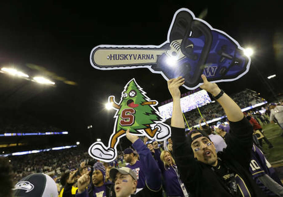 Washington fans hold up images of a chainsaw and the Stanford tree mascot as they rush the field following an NCAA college football game, Friday, Sept. 30, 2016, in Seattle. Washington defeated Stanford 44-6. (AP Photo/Ted S. Warren)