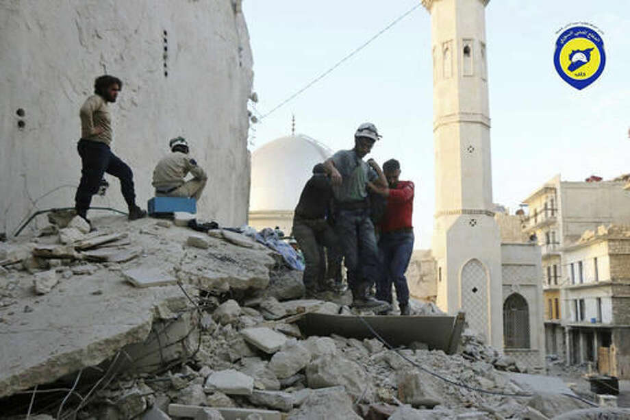 This Tuesday, Oct. 4, 2016 photo, provided by the Syrian Civil Defense group known as the White Helmets, shows Civil Defense workers from the White Helmets carry a body as they walk on the rubles of a destroyed building after airstrikes hit the Bustan al-Basha neighborhood in Aleppo, Syria. The U.N. on Wednesday released stark satellite images showing the most recent destruction of Syria's embattled northern city of Aleppo, pounded by Syrian and Russian airstrikes since the collapse of a U.S.-Russia brokered cease-fire two weeks ago. (Syrian Civil Defense White Helmets via AP)