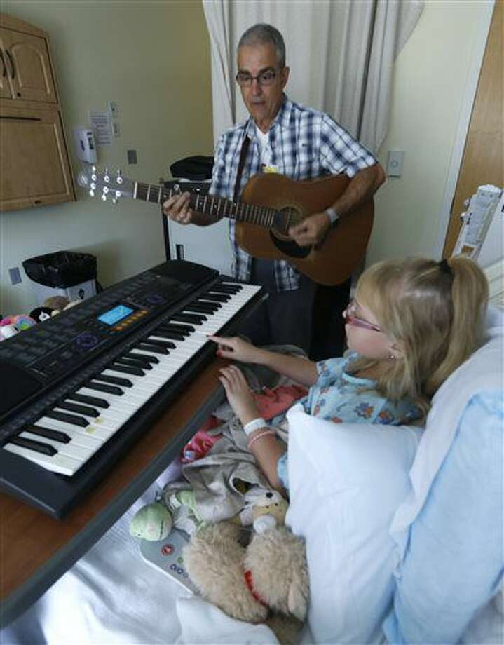 In a Sept. 9, 2016 photo, music therapist David Putano teaches Hannah Gorham, 9, how to play the piano during their first session at the ProMedica Toledo Children's Hospital in Toledo,Ohio. In ProMedica Toledo Children's Hospital since Aug. 31 for severe migraines, Hannah was introduced recently to music therapy, a growing practice for hospitalized children and those with developmental or physical disabilities. (Lori King/The Blade via AP)