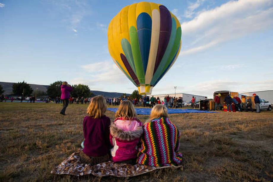 In this Friday, Sept. 23, 2016 photo, pilots, crew members and spectators gather at the airfield for the Great Prosser Balloon Rally in Prosser, Wash. McKenna Secrist's 16th birthday in July came with a hot air balloon pilot's license instead of a driver's license. Secrist joined more than a dozen hot air balloon pilots at the Great Prosser Balloon Rally, where they fired up their colorful conveyances at the Prosser Airport. (Shawn Gust/Yakima Herald-Republic via AP)
