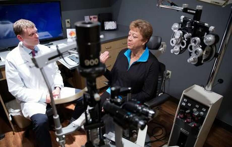 In this Friday, Sept. 16, 2016 photo, Dr. Lance Kugler chats with Cheryl Henry during a follow-up visit at Kugler Vision, in Omaha, Neb. (Rebecca Gratz/Omaha World-Herald via AP)