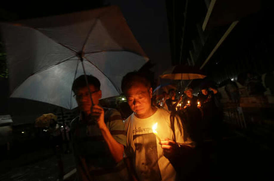 Thai activists hold lighted candles at Thammasat University in Bangkok, Thailand, Thursday, Oct. 6, 2016. Buddhist monks, mourners, activists and others gathered Thursday to mark the 40th anniversary of one of the darkest days in Thailand's history, when police killed scores of university students at a peaceful protest, and ghoulish vigilantes defiled the dead. (AP Photo/Sakchai Lalit)