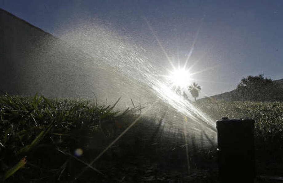 FILE - In this June 23, 2015, file photo, a lawn is irrigated in Sacramento, Calif. State regulators said Wednesday, Oct. 5, 2016, water conservation continues to slip in drought-stricken California after officials lifted mandatory cutbacks. (AP Photo/Rich Pedroncelli, File)