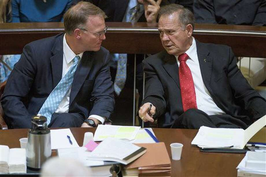 Embattled Alabama Chief Justice Roy Moore talks with his attorney Philip Jauregui during Moore's ethics trial before the Alabama Court of the Judiciary at the Alabama Judicial Building in Montgomery, Ala., on Wednesday Sept. 28, 2016. (Mickey Welsh/Montgomery Advertiser via AP)