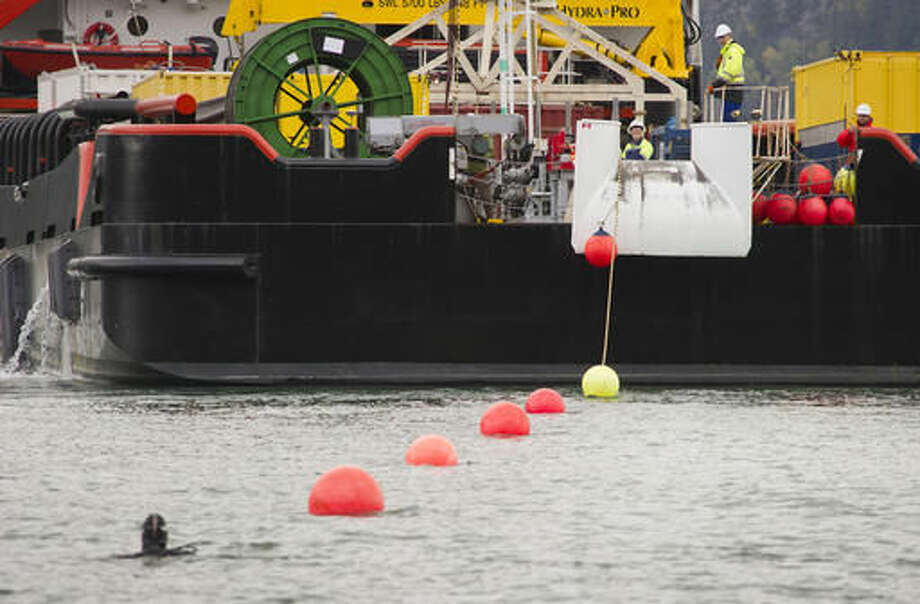 This Sept. 23, 2016 photo shows floats attached to a fiber optic cable as it is brought to shore by the modified supply ship Silver Arrow in Haines, Alaska, for the Alaska Power and Telephone Company. The cable is the first fiber-optic link between Juneau and the northern end of Lynn Canal and the first significant undersea fiber link constructed by AP&T. When it begins operating in mid-October, it will bring faster, more reliable internet service to Haines and Skagway, and possibly to Juneau and the Yukon. (Michael Penn /The Juneau Empire via AP)