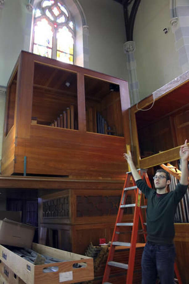 In this Wednesday, Oct. 5, 2016, photo, music director Cody Mead points to where organ pipes have been removed from in front of the stained glass windows in the choir loft of St. Mary's Church in Newport, R.I. The church where John F. Kennedy and Jacqueline Bouvier married is being restored to the appearance it had when they wed on Sept. 12, 1953. (AP Photo/Michelle R. Smith)