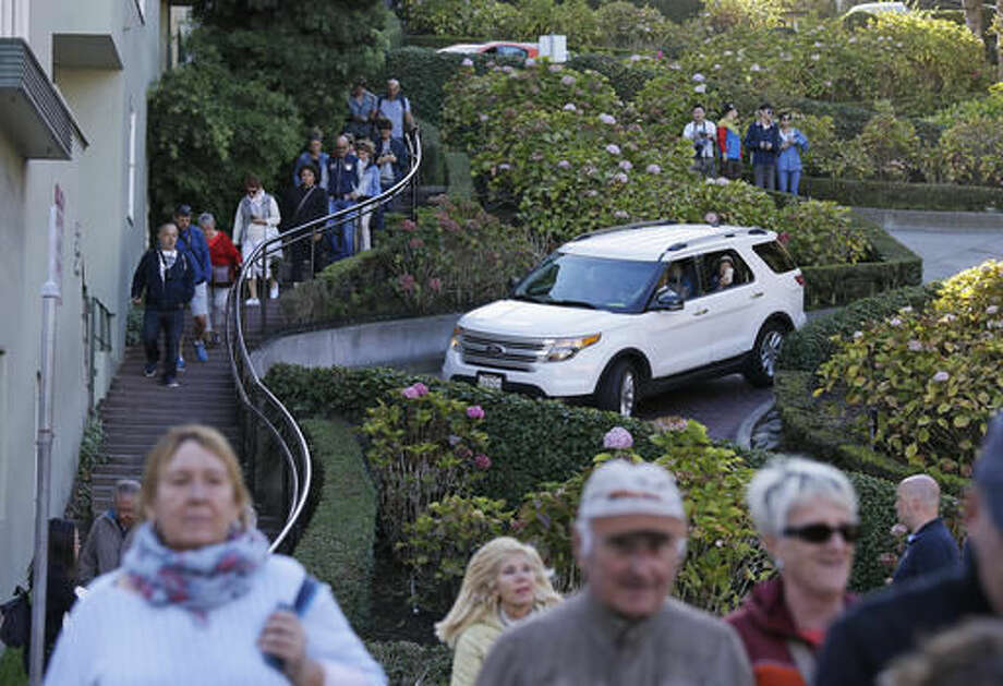 """In this photo taken Wednesday, Sept. 21, 2016, tourists make their way down Lombard Street, also known as the """"most crooked street"""" in San Francisco. The crooked block has become so chaotic that the city of San Francisco is considering solutions as drastic as banning cars, requiring reservations or charging a toll to the cars wishing to drive down the stretch of winding street to try to bring order to one of the world's most famous streets. (AP Photo/Eric Risberg)"""