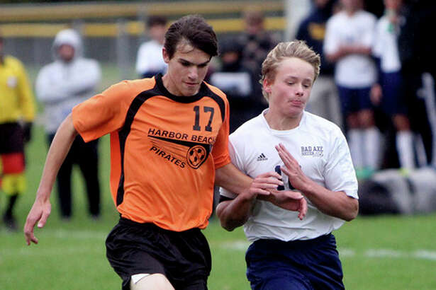 Seth Stapleton/Huron Daily Tribune   Above, Bad Axe's Justin Shemka (16) and Harbor Beach's Paul Rayment (17) go after a ball during the first half of the Hatchets' 2-1 double overtime victory, Thursday, in Bad Axe.