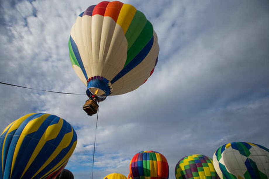 In this Friday, Sept. 23, 2016 photo, pilots, crew members and spectators gather at the airfield for the Great Prosser Balloon Rally in Prosser, Wash. McKenna Secrist's 16th birthday in July came with a hot air balloon pilot's license instead of a driver's license. Secrist joined more than a dozen hot air balloon pilots at the Great Prosser Balloon Rally, where they fired up their colorful conveyances at the Prosser Airport. (Shawn/Yakima Herald-Republic via AP)