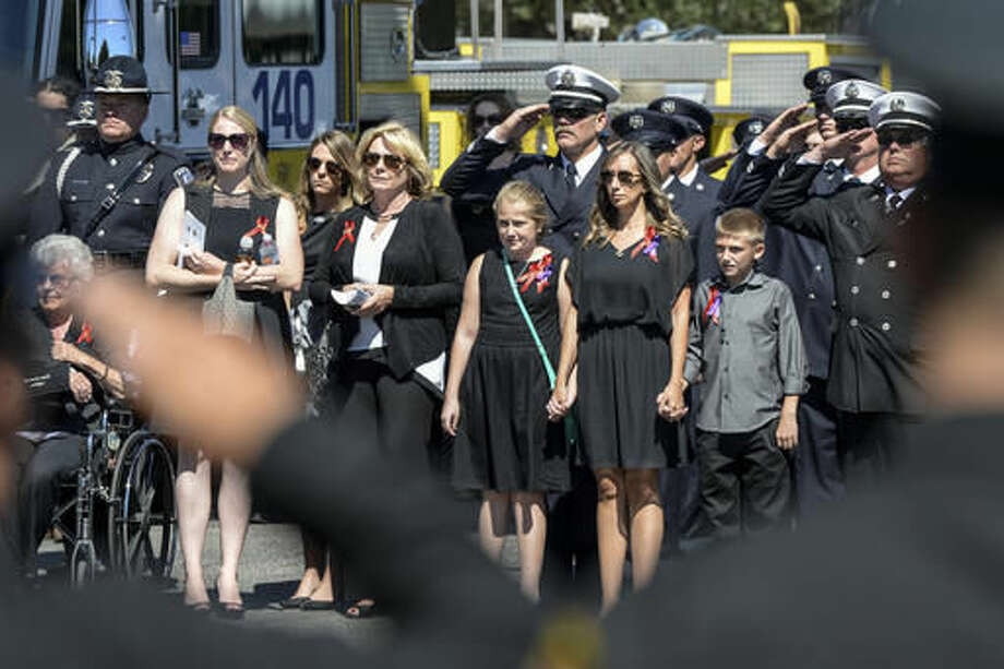 The family of Ventura County Fire Engineer Ryan Osler looks on as the flag draped coffin is carried to a fire truck for his final trip during ceremonies Monday, Oct. 3, 2016. Osler was killed in a an accident while on duty on September 21, 2016. Hundreds of firefighters from around the state attended the services. (David Crane/Los Angeles Daily News via AP)