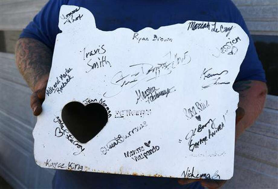In this Sept. 16, 2016 photo, Justin Troxel holds a larger version of the stamped metal Oregon memorial plates he began crafting last year that is signed by many of the community volunteers that helped out, in Roseburg, Ore. For some Douglas County residents, the days after the Oct. 1, 2015 mass shooting at Umpqua Community College inspired them to use their skills to bring the community together, or to raise funds for the families who suffered most. (Michael Sullivan/The News-Review via AP)