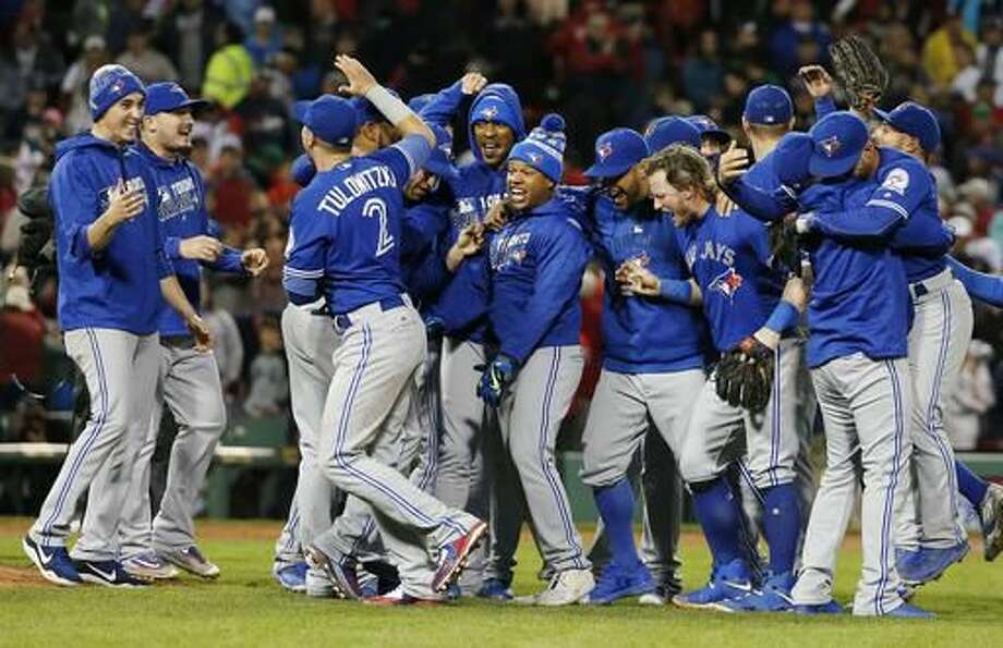The Toronto Blue Jays celebrate after defeating the Boston Red Sox 2-1 during a baseball game in Boston, Sunday, Oct. 2, 2016. (AP Photo/Michael Dwyer)