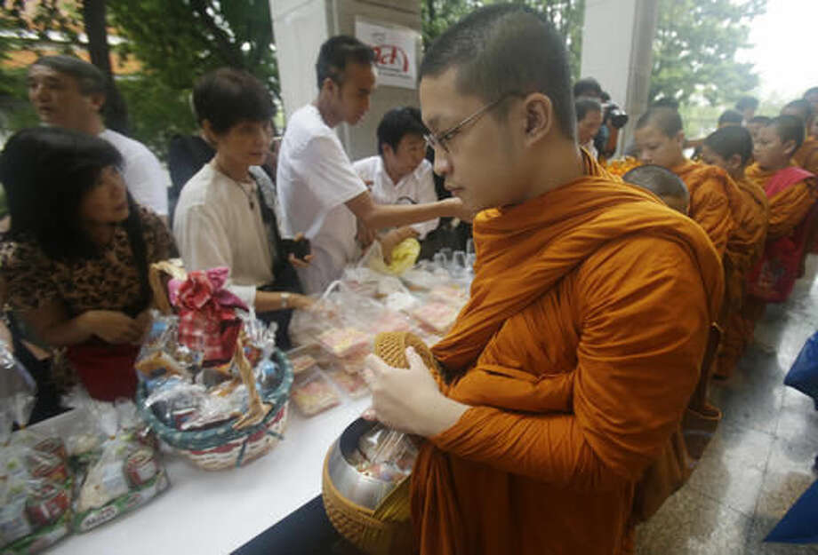 Thai people offer food to monks at Thammasat University in Bangkok, Thailand, Thursday, Oct. 6, 2016. Buddhist monks, mourners, activists and others gathered Thursday to mark the 40th anniversary of one of the darkest days in Thailand's history, when police killed scores of university students at a peaceful protest, and ghoulish vigilantes defiled the dead. (AP Photo/Sakchai Lalit)
