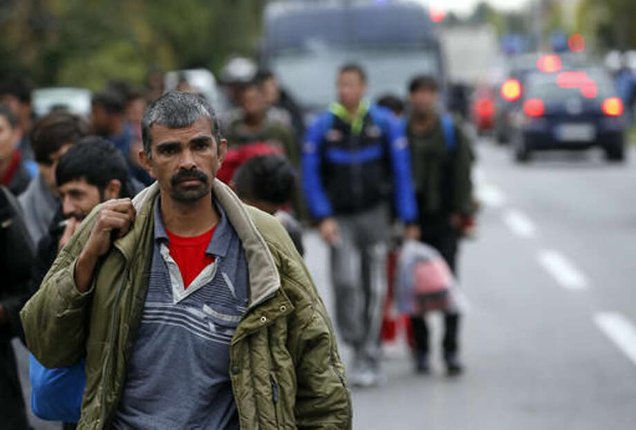 Migrants and refugees walk toward the Serbian border with Hungary in the village of Nova Pazova, some 30 kilometers (20 miles) west of Belgrade, Serbia, Tuesday, Oct. 4, 2016. Hundreds of migrants stranded in Serbia set off on foot on Tuesday toward the border with Hungary to protest its closure for most people trying to reach the European Union. (AP Photo/Darko Vojinovic)