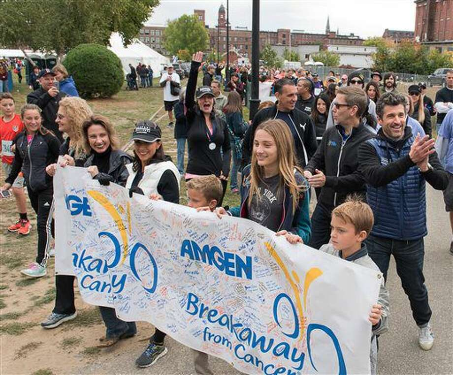 """Actor Patrick Dempsey, right, applauds a group of supporters cheering for him and a long line of cancer survivors in a parade prior to the start of the bike-and-run """"Dempsey Challenge"""" Saturday, Oct. 1, 2016 in Lewiston, Maine. The Maine native, who plays a starring role in the new romance-comedy, """"Bridget Jones's Baby,"""" participated Saturday in a cancer survivor walk with his three children and two sisters. (Russ Dillingham/The Lewiston Sun-Journal via AP)"""