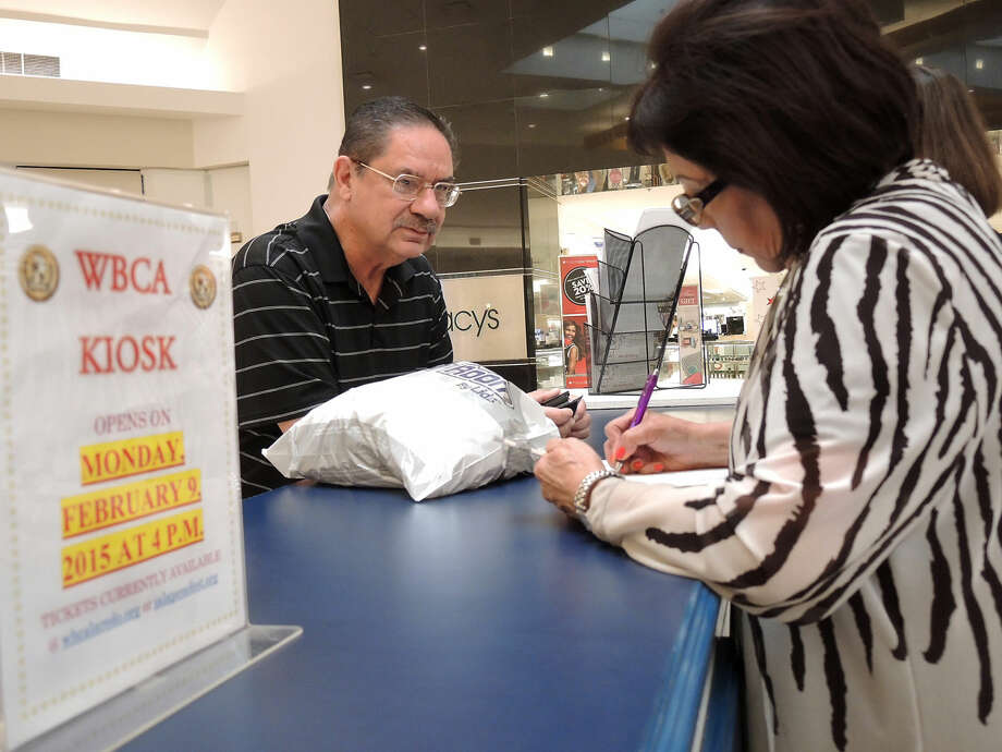 Fernando Tijerina speaks with Gloria Ambrose, of WBCA, while purchasing tickets for the WBCA Stars and Stripes Air Show Spectacular on Monday afternoon at the WBCA Ticket Kiosk at Mall del Norte. (Photo by Cuate Santos/Laredo Morning Times)