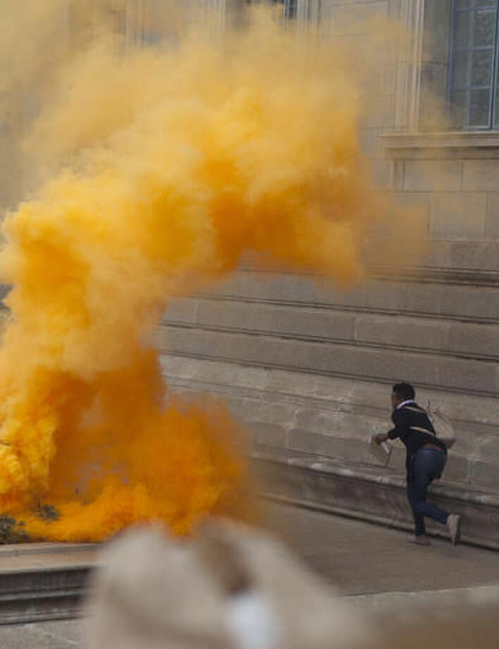 A woman on a campus of the University of the Witwatersrand runs from teargas , in Johannesburg, Tuesday, Oct. 4, 2016, during clashes with police and private security officers. Police fired rubber bullets and set off stun grenades to disperse the protesters after the university announced it was re-opening despite sometimes violent demonstrations for free education. (AP Photo/Wikus de Wet)