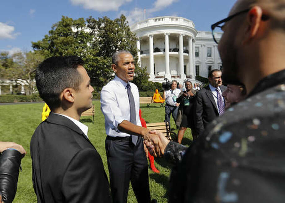 President Barack Obama shakes hands as he surprises guests attending South by South Lawn at the White House in Washington, Monday, Oct. 3, 2016. The festival is inspired by Austin's South by Southwest, with art, film and music performances and hosted by Obama. (AP Photo/Pablo Martinez Monsivais)