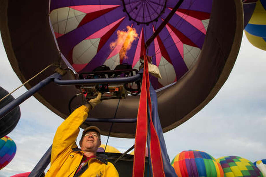 In this Friday, Sept. 23, 2016 photo, Scott Shields, a hot air balloon pilot from Ferndale, Wash., fires the burner of his son's balloon during the kick-off of the Great Prosser Balloon Rally in Prosser, Wash. McKenna Secrist's 16th birthday in July came with a hot air balloon pilot's license instead of a driver's license. The Yakima Herald-Republic reports the Bothell teen is a welcome addition to a pastime that often struggles to recruit younger enthusiasts to replace retiring pilots. (Shawn Gust/Yakima Herald-Republic via AP)